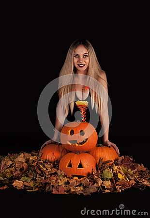 Charming witch with funny pumpkins and leaves