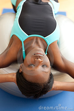 Charming woman doing sit-ups with a pilates ball