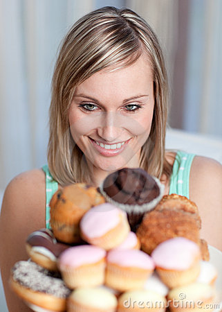Charming woman holding a plate of cakes