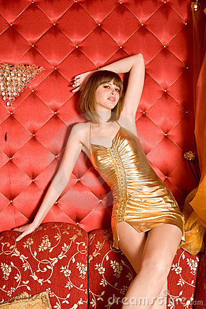 Free Charming Woman Sitting On Red Couch Royalty Free Stock Photography - 11447867
