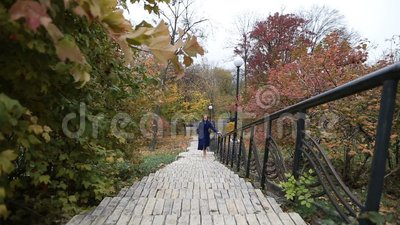 Charming woman walking up the stairs in fall stock footage