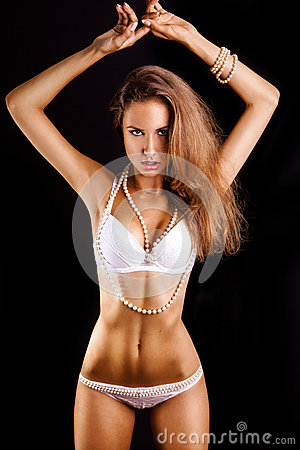 Charming woman in white lingerie on black background