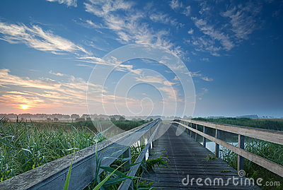 Charming wooden bridge over river at misty sunrise