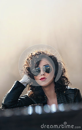 Free Charming Young Curly Brunette Woman With Sunglasses And Black Leather Jacket Against Wall. Sexy Gorgeous Young Woman Stock Photos - 67044933
