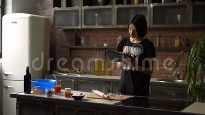 Housewife reading recipe on tablet in the kitchen stock footage