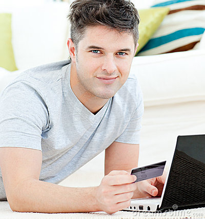 Charming young man with card and laptop lying