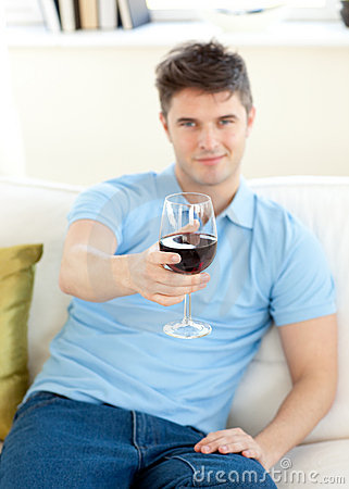 Charming young man on a sofa holding wineglass