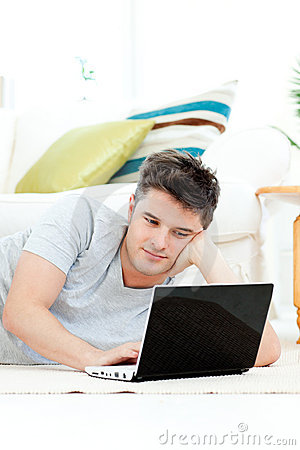 Charming young man using his laptop on the floor