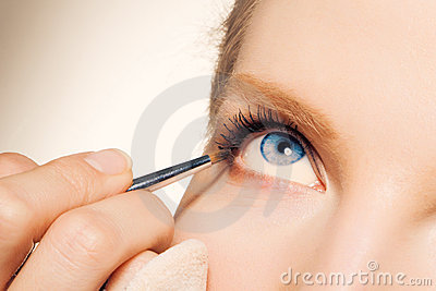 Charming young woman applying blusher eyelid
