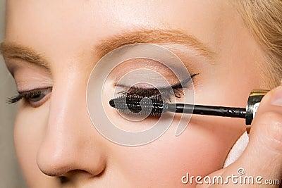 Charming young woman applying blusher eyelid
