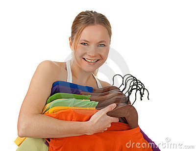 Charming young woman holding colourful clothes