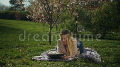Charming young woman reading a book in spring park stock video footage