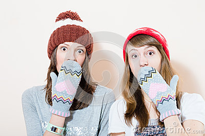 2 charming young women in winter caps gloves puzzled looking in camera on white background portrait