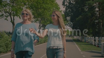 Chatting senior mother and adult daughter walking in park. Chatting beautiful senior mother with elegant adult daughter walking along park alley on sunny summer stock video