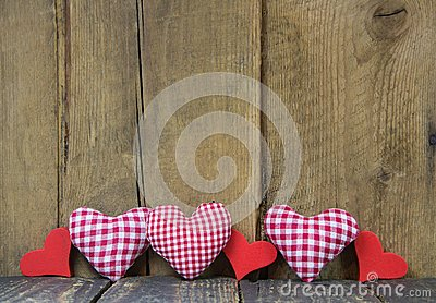 Checkered hearts on wooden background.