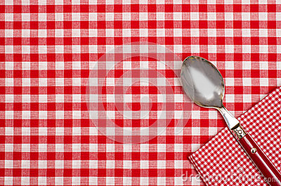Checkered table cloth with red and white checks and a spoon