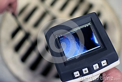 Checking sewer manhole with borescope inspection camera. Stock Photo
