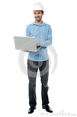 Cheeful builder surfing on his laptop