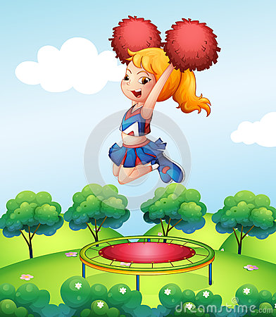 A cheerdancer holding her red pompoms above the trampoline