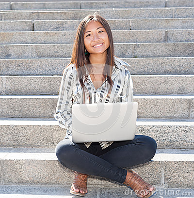 Cheerful asian girl working on laptop outdoor