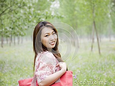Cheerful asian woman carrying shopping bag