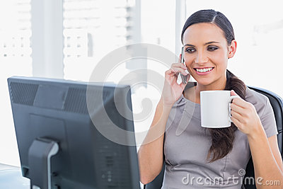 Cheerful attractive businesswoman holding coffee and answering p
