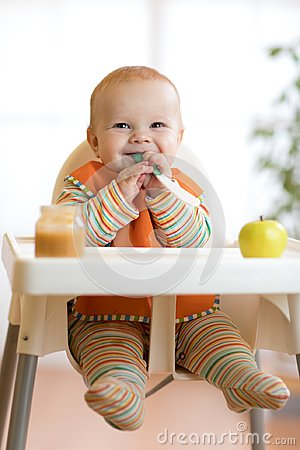 Free Cheerful Baby Child Eats Food Itself With Spoon. Portrait Of Happy Kid Boy In High-chair. Stock Photo - 105327850