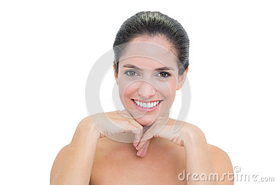 Cheerful bare brunette touching her chin