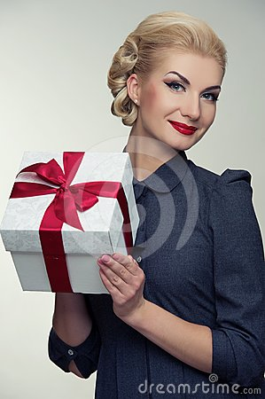 Cheerful blond woman in grey dress with box