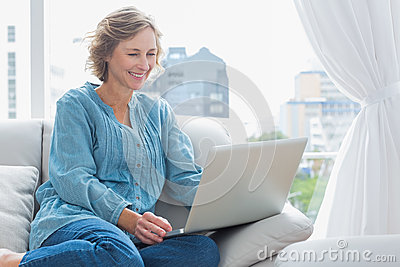 Cheerful blonde woman sitting on her couch using laptop