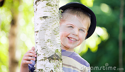 Cheerful boy hiding himself in the garden