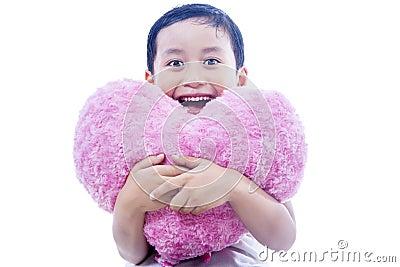 Cheerful boy holding heart pillow