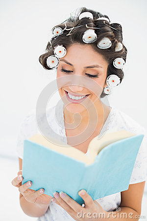 Cheerful brunette in hair rollers reading a book on bed