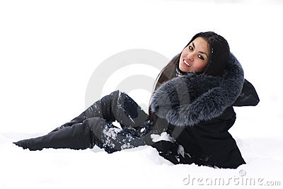 Cheerful brunette sitting on snow