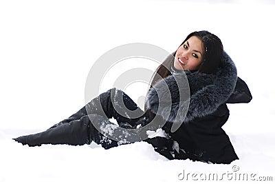 Cheerful brunette sitting on snow
