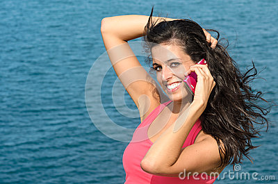 Cheerful brunette using phone in summer