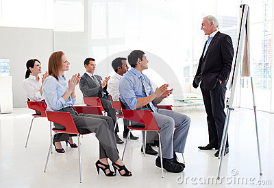 Cheerful business people clapping at a conference