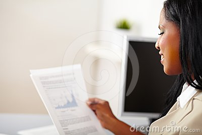 Cheerful business woman reading documents