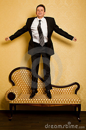 Cheerful businessman jumping on sofa