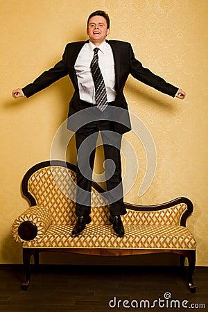 Cheerful businessman jumping on sofa