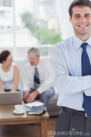 Cheerful businessman standing while his colleagues are working