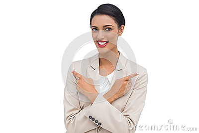 Cheerful businesswoman with her arms crossed and fingers pointin