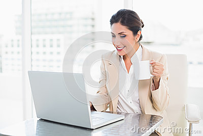 Cheerful businesswoman holding mug while working on laptop