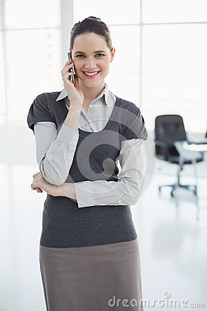 Cheerful businesswoman on the phone posing
