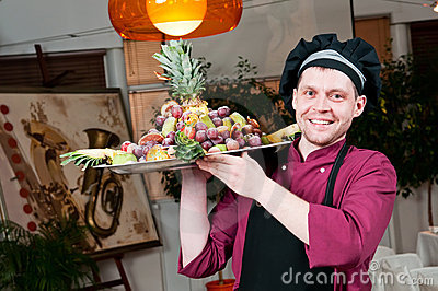 Cheerful chef cook with fruits
