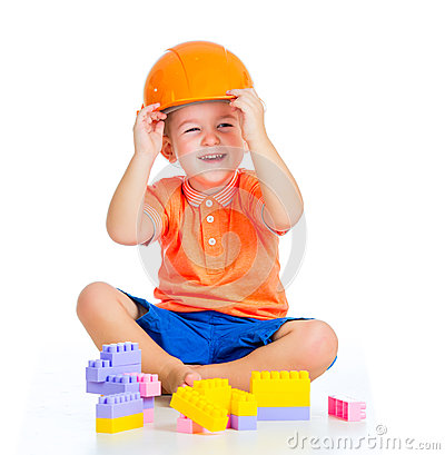Cheerful child boy with hard hat plays with building blocks toys