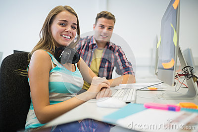 Cheerful classmates doing assignment together in the computer room