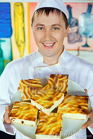 Cheerful cook holding cheese baked pudding on dish