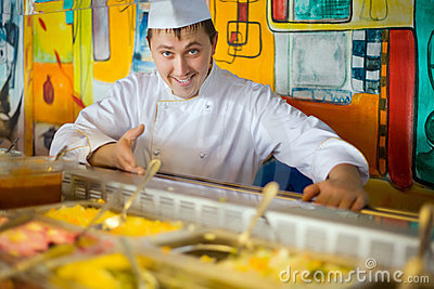 Cheerful cook in uniform near counter with meal
