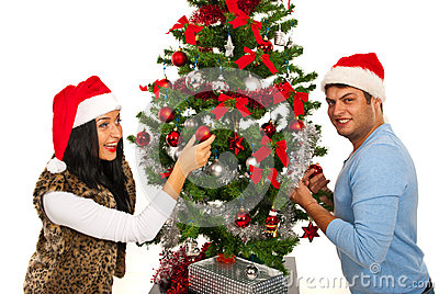 Cheerful couple decorate tree
